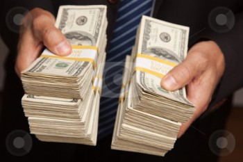 cutcaster-photo-100651424-Businessman-Handing-Over-Stacks-of-Money