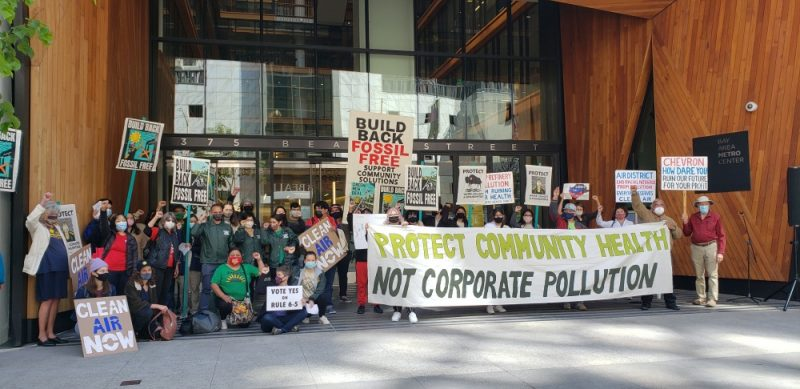 """Community members in favor of Rule 6-5 gather for a group picture in front of BAAQMD's headquarters in San Francisco with several signs. One major banner reads, """" protect community health, not corporate wealth"""""""